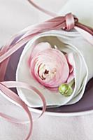 Pink ranunculus wrapped in linen napkin tied with