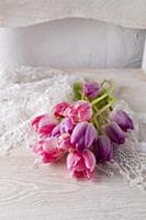 Pink and purple tulips on lace doily on white chai