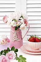 Metal jug of delicate pink roses and china bowl of