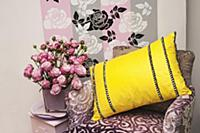 A purple velvet chair with a yellow cushion, vase