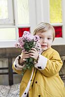 Boy wearing yellow jacket holding bunch of flowers