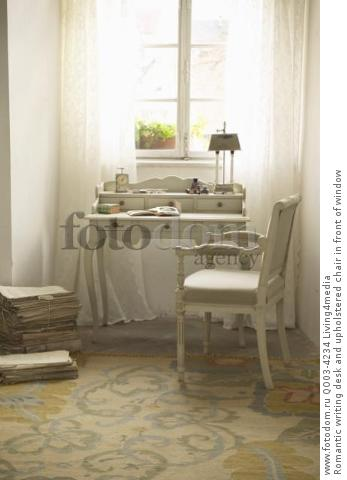 Romantic writing desk and upholstered chair in front of window