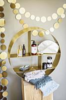 Golden garland above round shelving unit containin