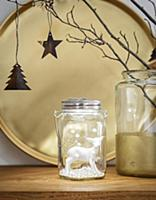 White deer figurine in jar in front of gold tray
