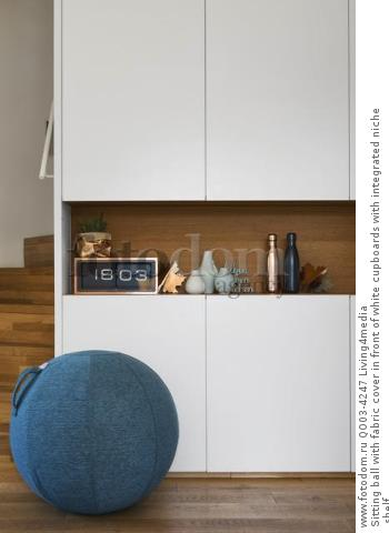 Sitting ball with fabric cover in front of white cupboards with integrated niche shelf