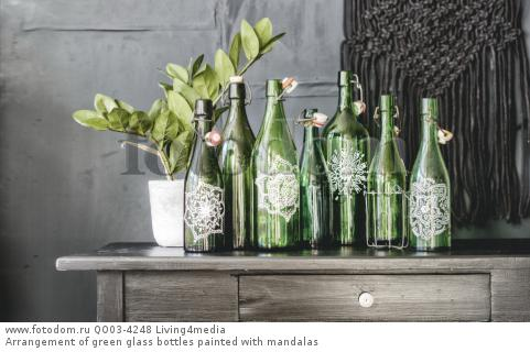 Arrangement of green glass bottles painted with mandalas