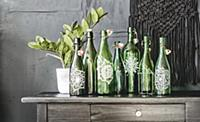 Arrangement of green glass bottles painted with ma