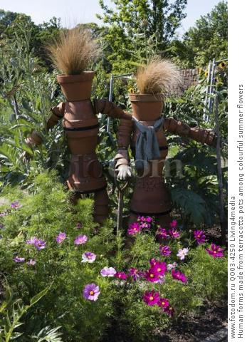 Human forms made from terracotta pots among colourful summer flowers