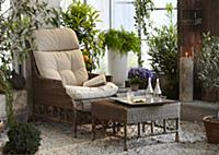 Wicker chair in pleasant seating area amongst lush