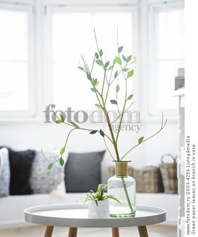 Green paper leaves on branch in vase