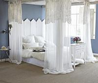Blue walls and white four-poster bed in romantic b