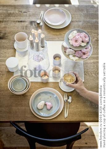 Hand placing a cup of coffee on a romantically set table