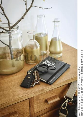Note book and key chain in front of bottles painted gold