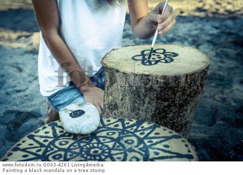 Painting a black mandala on a tree stump