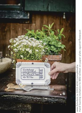 Hand leaning invitation to BBQ written on paper plate against flowerpot