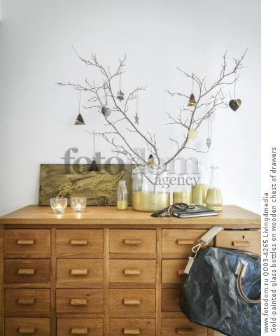 Gold-painted glass bottles on wooden chest of drawers