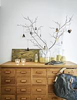 Gold-painted glass bottles on wooden chest of draw