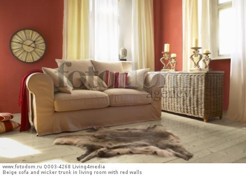 Beige sofa and wicker trunk in living room with red walls
