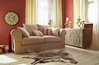 Beige sofa and wicker trunk in living room with re