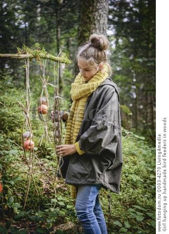 Girl hanging up handmade bird feeders in woods