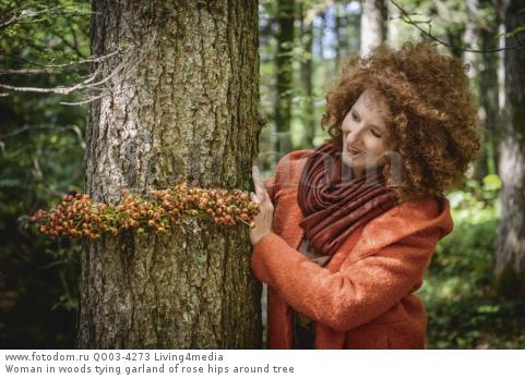 Woman in woods tying garland of rose hips around tree