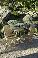 Wooden garden furniture in seating area of Mediter