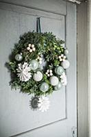 Festive door wreath with paper snowflakes and baub