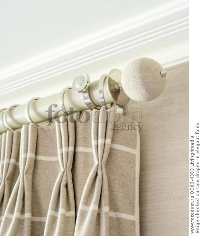 Beige checked curtain draped in elegant folds