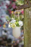 Petunias and rose in suspended egg used as vase