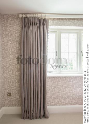 Grey curtain draped in elegant folds against spotted wallpaper