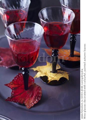 Wine glasses decorated with colourful, painted autumn leaves