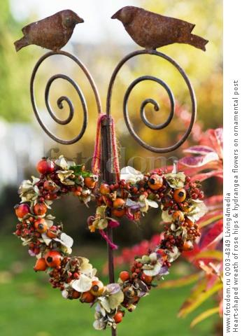 Heart-shaped wreath of rose hips & hydrangea flowers on ornamental post
