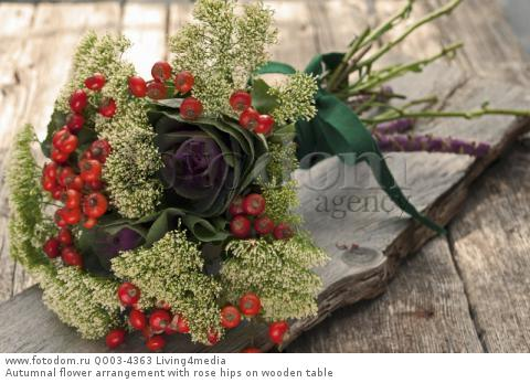 Autumnal flower arrangement with rose hips on wooden table