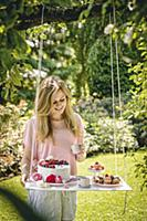 Woman stood next to cakes on DIY suspended table i