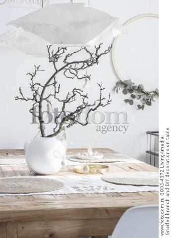 Gnarled branch and DIY decorations on table