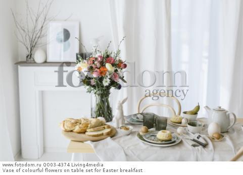 Vase of colourful flowers on table set for Easter breakfast