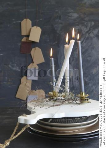 Lot candles on stacked crockery in front of gift tags on wall