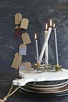 Lot candles on stacked crockery in front of gift t