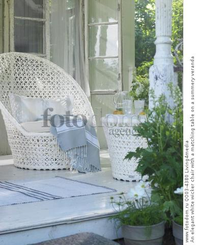 An elegant white wicker chair with a matching table on a summery veranda
