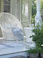 An elegant white wicker chair with a matching tabl