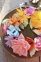 Wreath of colourful paper flowers on plate in suns