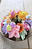 Chick decorations on wreath of colourful paper flo
