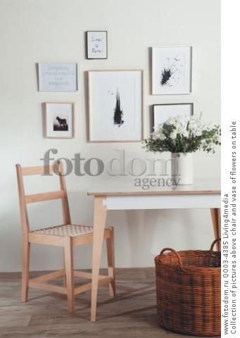 Collection of pictures above chair and vase of flowers on table