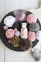 Geisha figurine and pompoms in pink and earthy ton