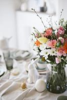 Vase of colourful flowers on Easter breakfast tabl
