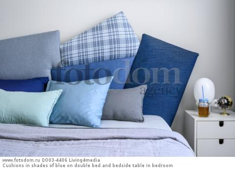 Cushions in shades of blue on double bed and bedside table in bedroom