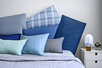 Cushions in shades of blue on double bed and bedsi