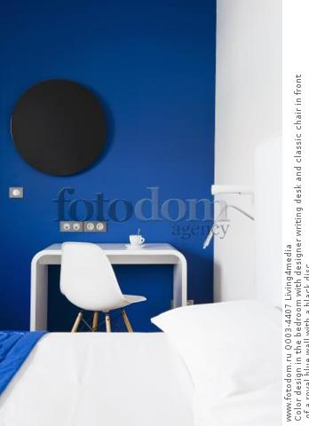 Color design in the bedroom with designer writing desk and classic chair in front of a royal blue wall with a black disc