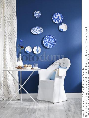 Small dining area with folding table and chair with loose cover against wall with blue wallpaper and blue and white decorative w