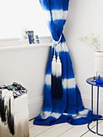 Blue and white curtain with tassels in corner of r